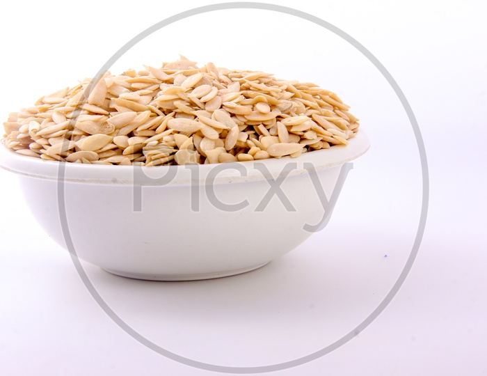 Dry Muskmelon Seeds in a Bowl on an Isolated White Background