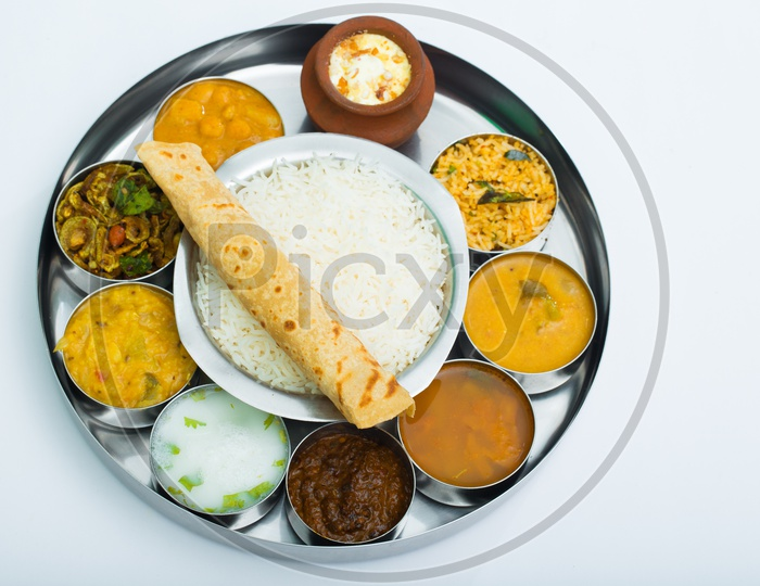 Indian Thali / Lunch / Dinner With Rice Bowl, Roti and Cups with Different Dishes Presentation Composition Shot with White Background