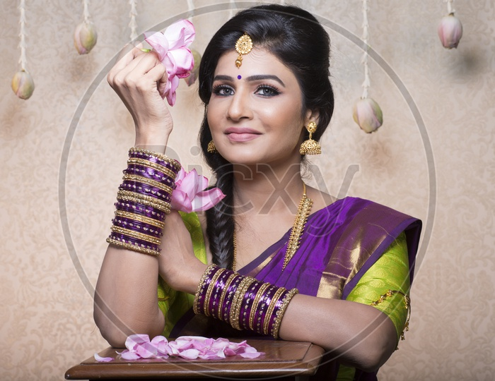Traditional Indian Female/Woman Model in Purple Saree, green Blouse with a Lotus flower in hand