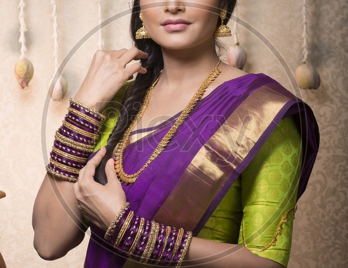 Traditional Indian Female/Woman Model in Purple Saree, green Blouse with a Lotus flower in hand - Smiling
