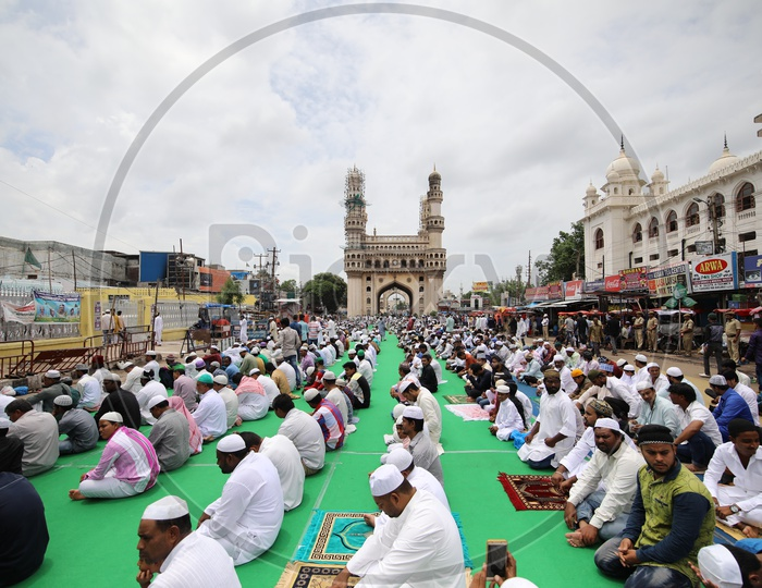 People doing namaz in charminar streets with charminar in the background