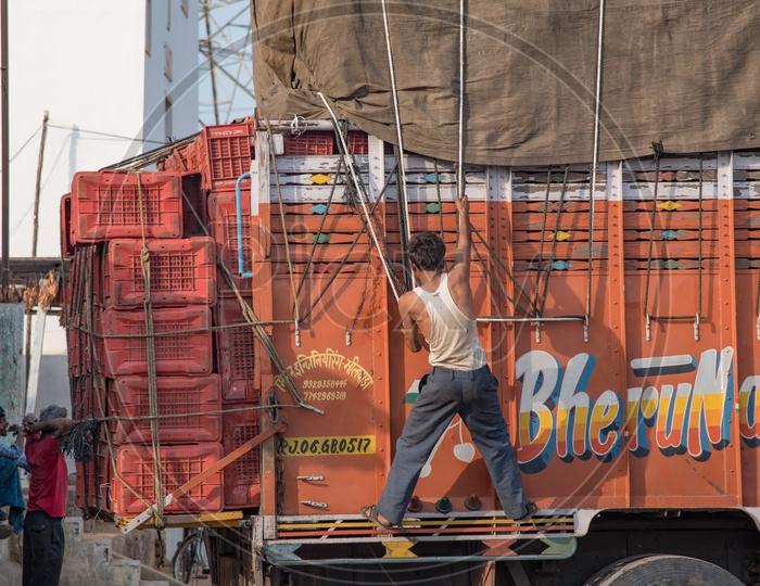 A Lorry Cleaner Tightening the tarpaulin cover on mango Load., Nunna mango Market.