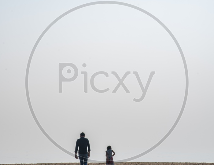 A Father,Daughter duo reaching out to the beach