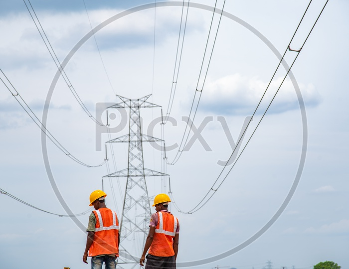 Construction Workers under High Voltage Electricity Wires.