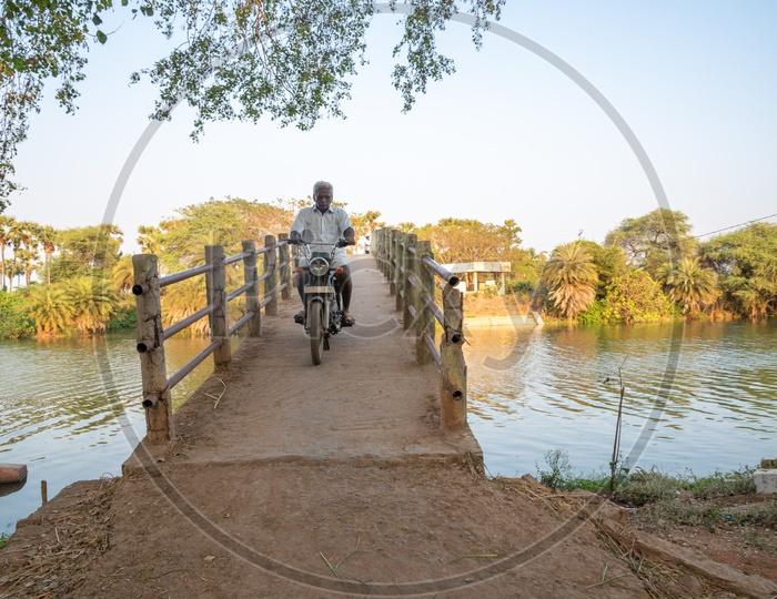 commuters using the small bridges on Buckingham Canal near Duggirala.