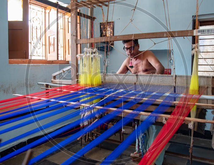 Artisan weaver working on hand operated spindle weaving machine to make sarees