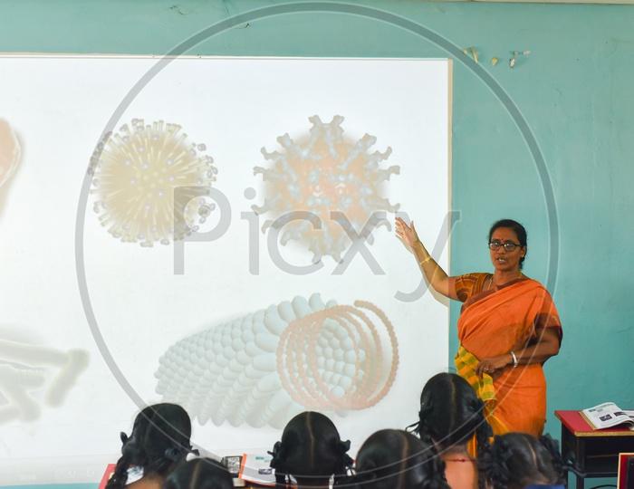 A teacher explaining taking a class on Virus through digital projections
