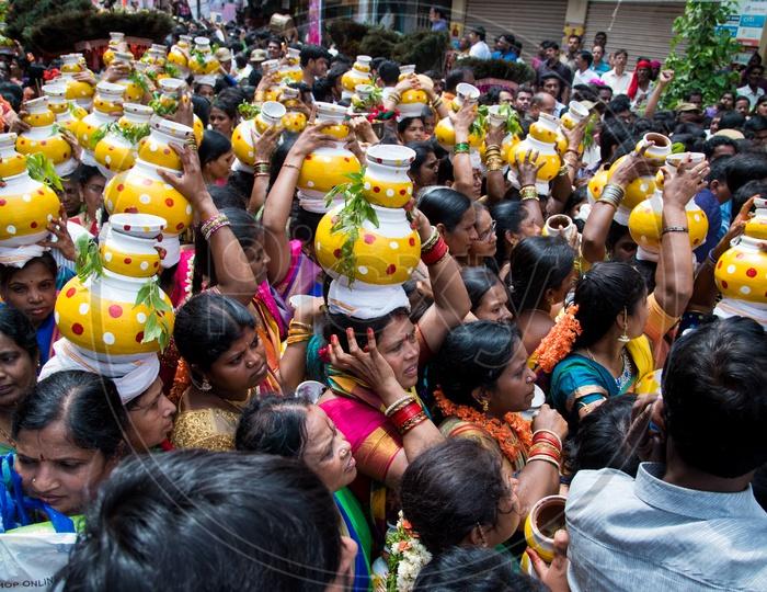Women carrying Bonam pot as offerings to Goddess Mahankali during Bonalu Festival