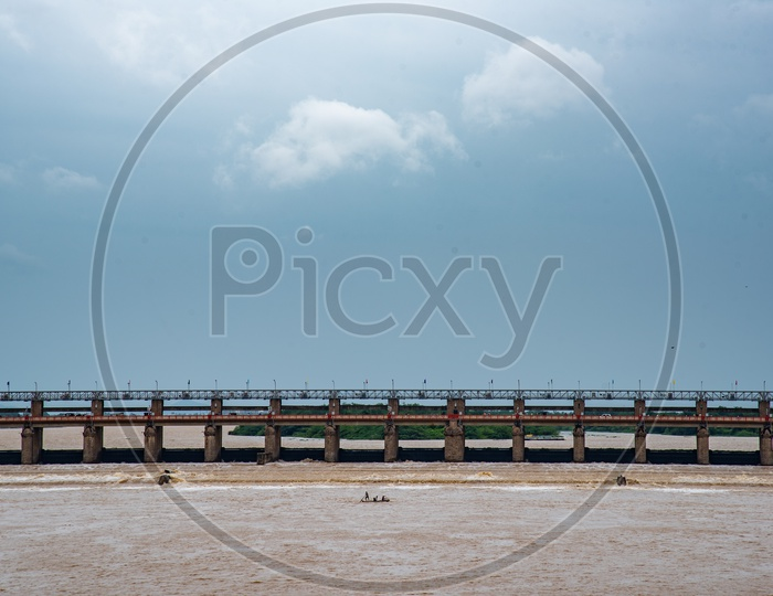 Fishermen Fishing on boats against the Current of Water at Prakasam Barrage