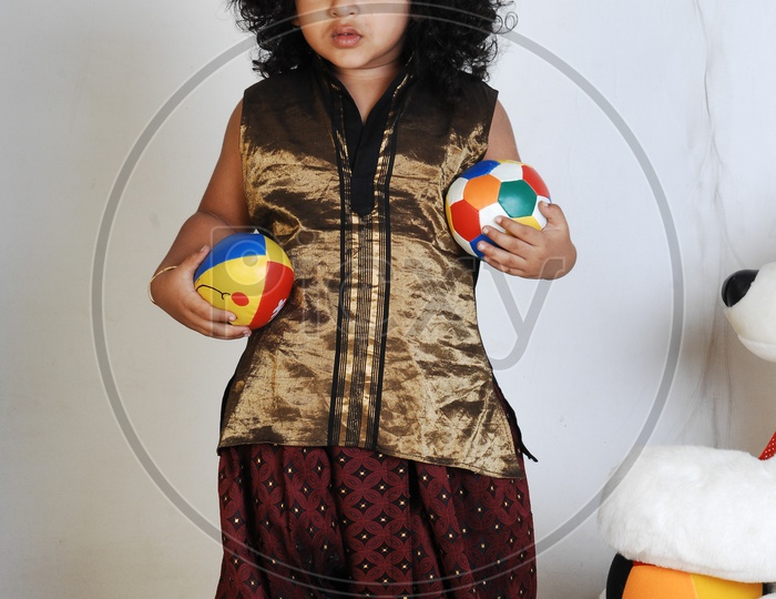 Indian Boy in Traditional Attire and With a Ball In Hand Over an Isolated White Background