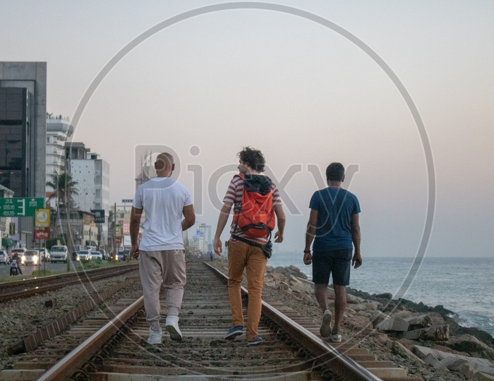 Tourist Friends walking on railway track by the beach in Colombo