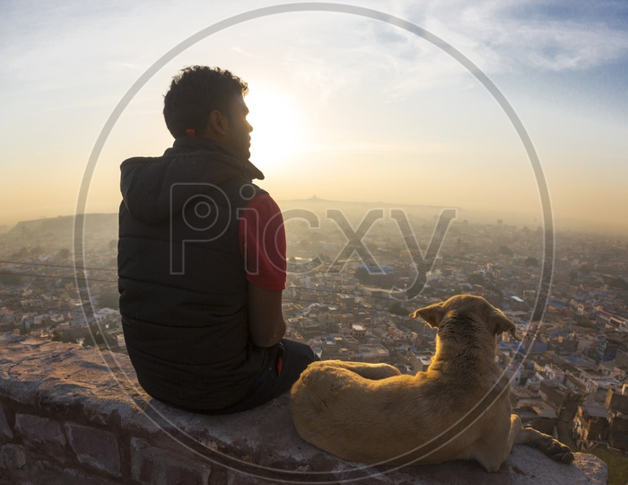 An Indian Man Sitting on a View Point In Mehrangarh Fort and Watching The Sunset Over The Jodhpur City witha Dog Besides Him