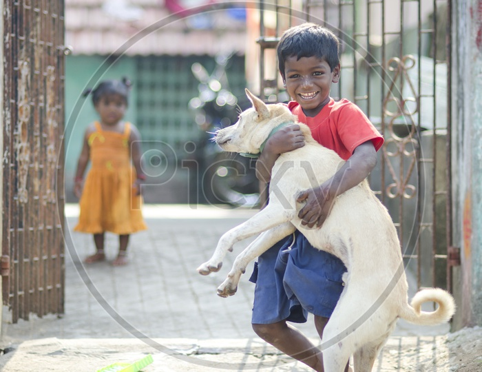 Indian kid holding dog in hands in the streets of Tamil Nadu