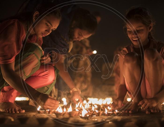Devotees lighting dia's on the eve of Dev Diwali.