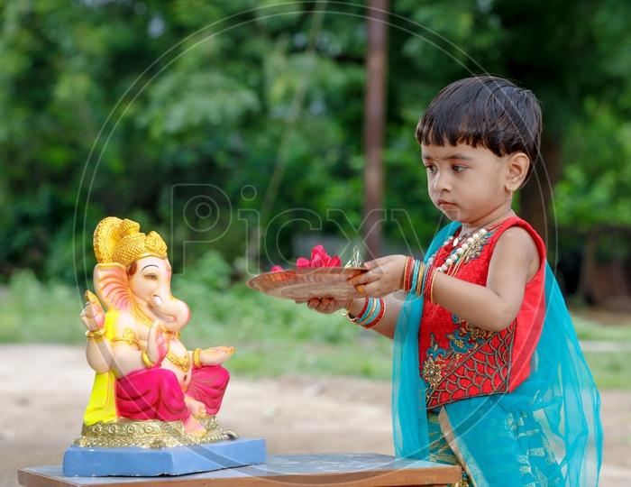 Indian Girl   Child  Offering  Prayer To Hindu Elephant Headed God Lord Ganesh
