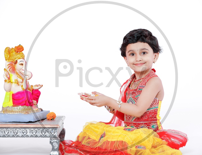 Indian Girl Child Offering Prayer to Lord Ganesh Statue On an Isolated White Background with Expression