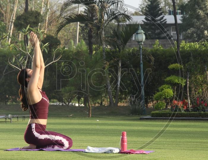 indian girl doing yoga in garden