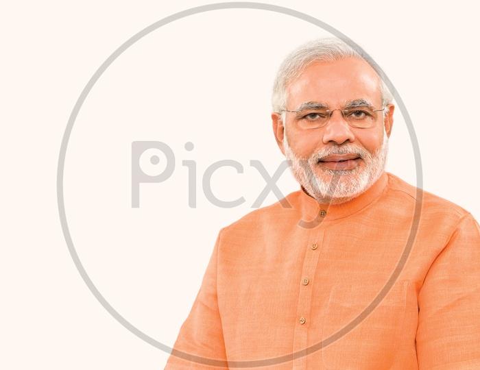 Prime Minister of India Narendra Modi smiling with white background in orange suit