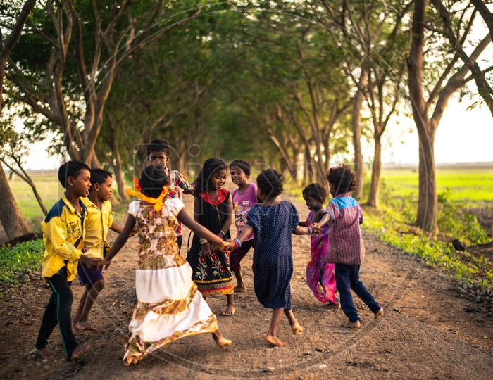 Under privileged kids playing on a rural village road without complaining of having  basic amenities