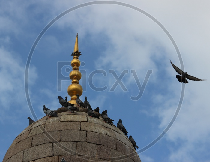 Mecca Masjid Dome With Pigeons With Sky in Background