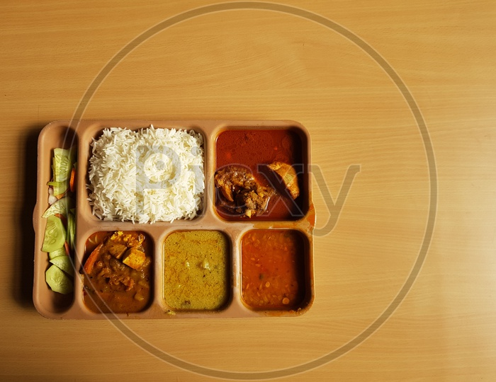Indian Chicken Thali With Rice Dal Chicken Salad Vegetable Curry On A Plastic Segmented Plate In Wooden Background
