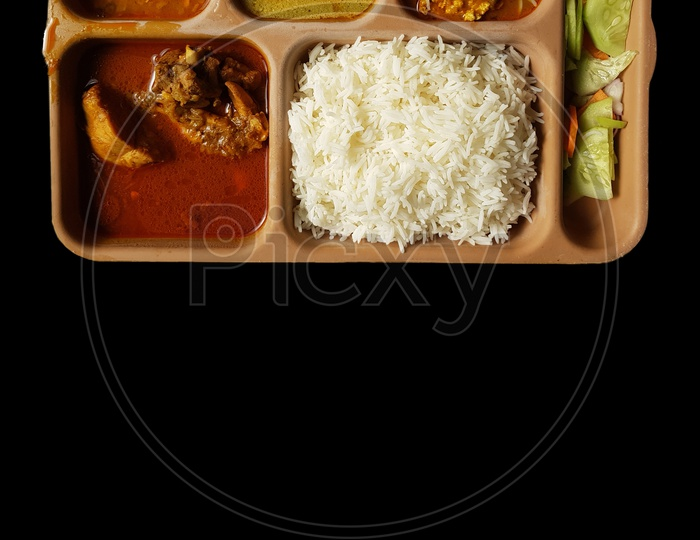 Indian Chicken Thali With Rice Dal Chicken Salad Vegetable Curry On A Plastic Segmented Plate In Black Background