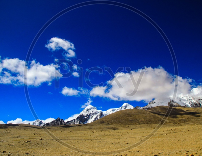 Landscape Of Deep Blue Sky And Ice Capped Peaks Of Himalayan Mountains With White Clouds During Day Time