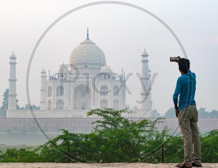 Man Capturing  Beautiful Taj Mahal on a Foggy Morning