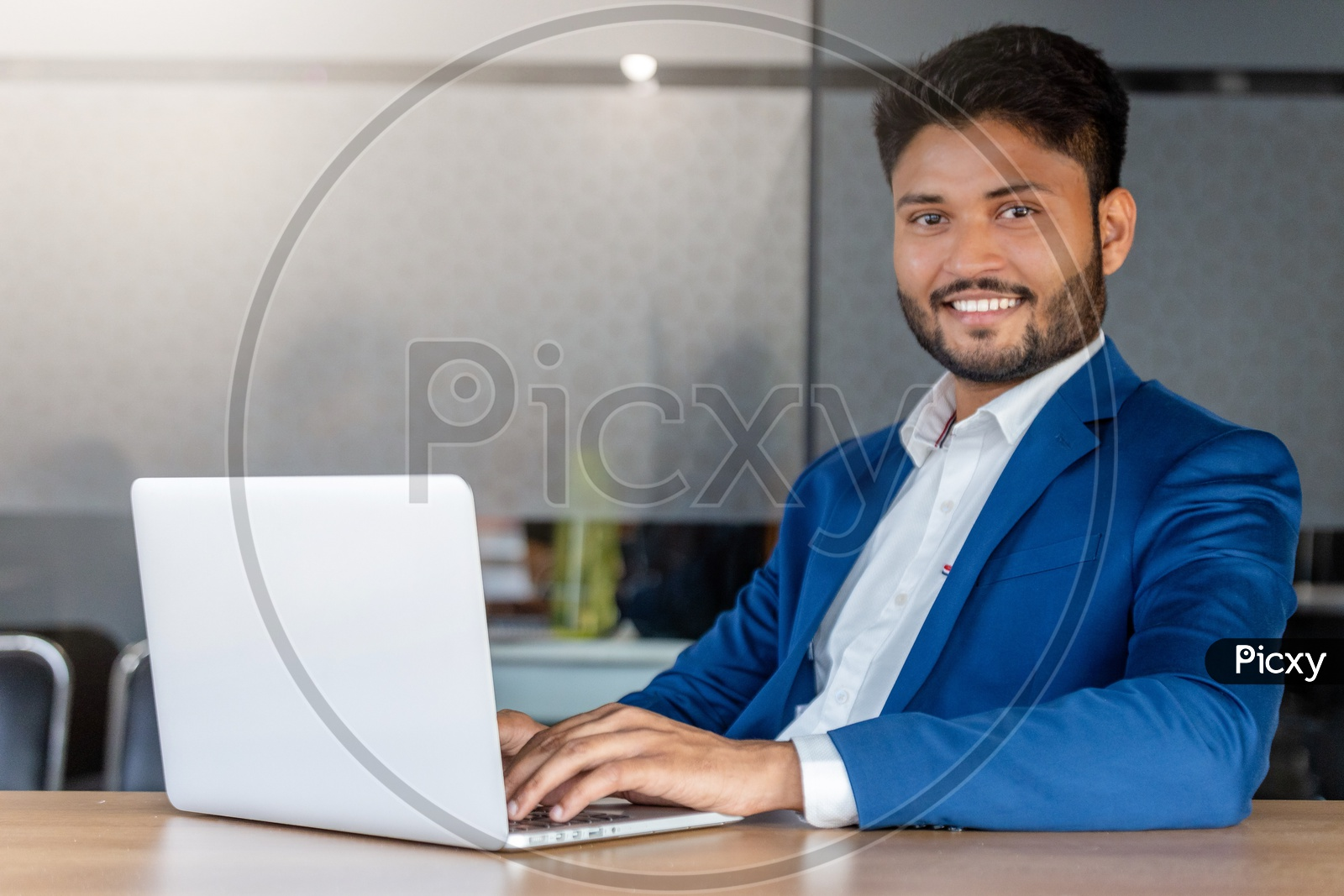Happy Indian Businessman Working On Laptop With Smile Face In Indoor