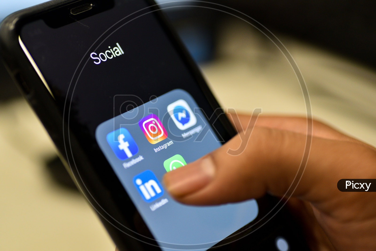 Social Networking Apps Installed In a Smartphone Icons Closeup With Man Finger Opening Linkedin App