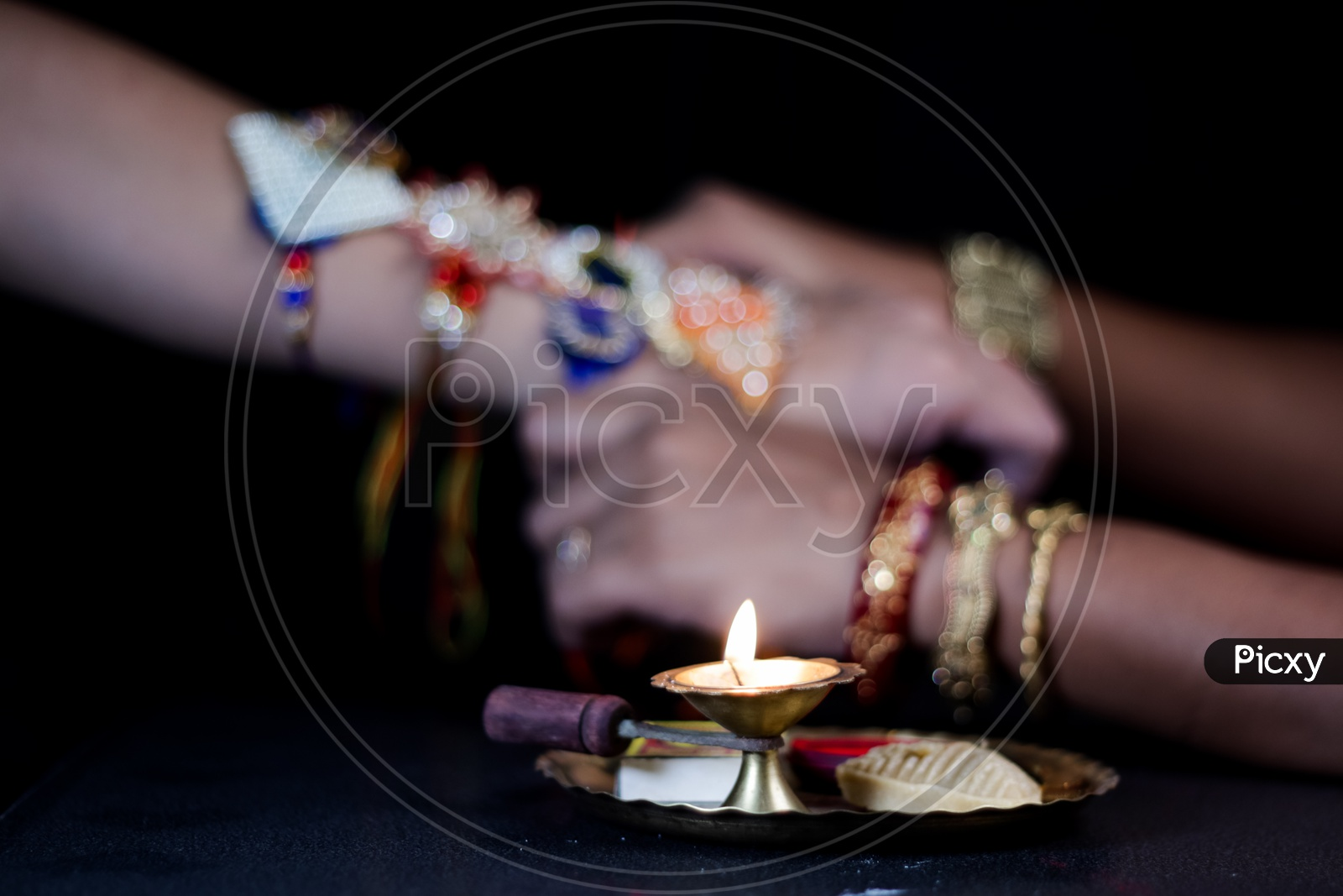 Elegant Rakhi Tied Hand Of a Guy  During Traditional Hindu Festival Raksha bandhan With Dia Bokeh Background