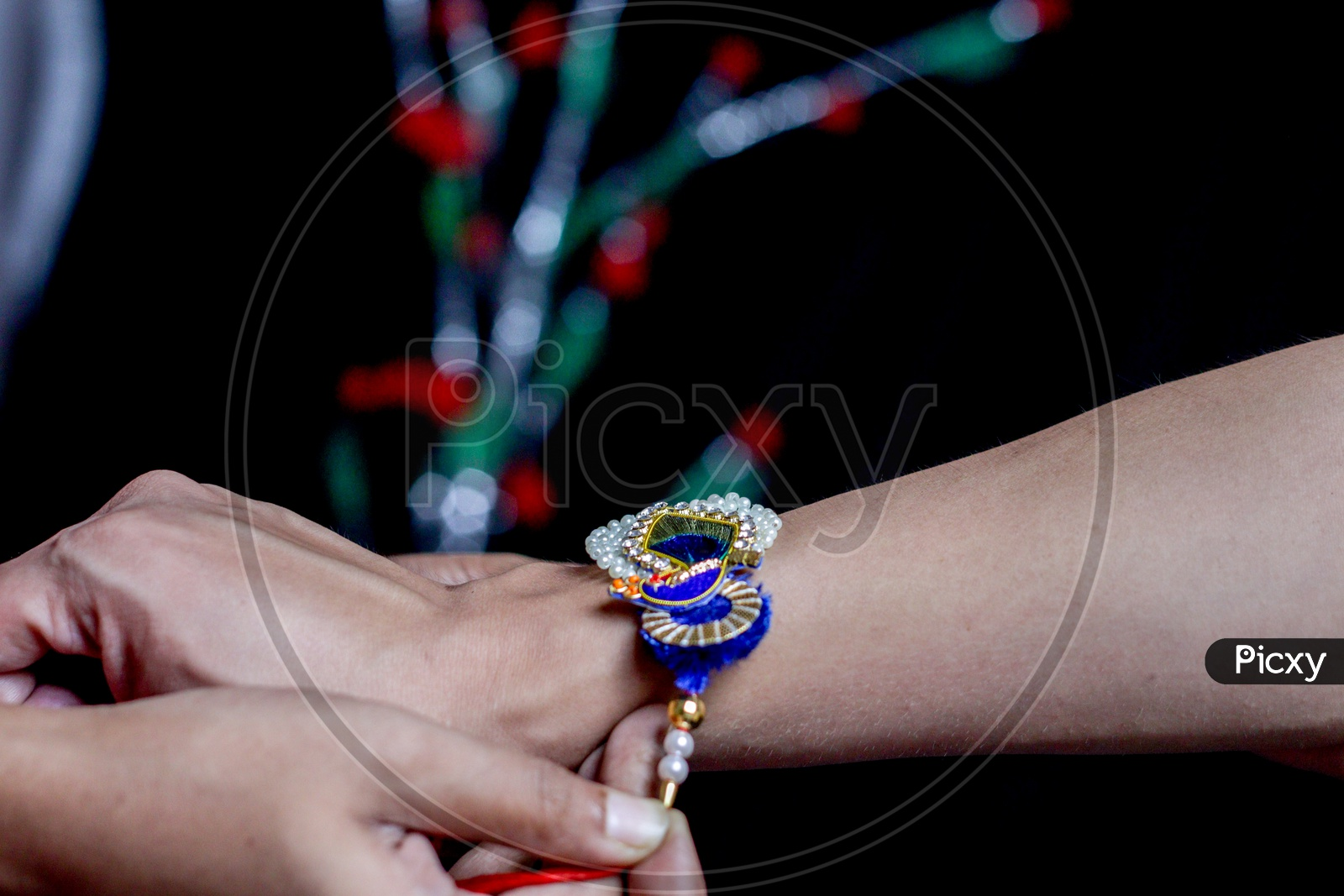Hand Of A Lady Tying Rakhi In Hand Of A Guy During The Hindu Ritual Of Rakshabandhan With Selective Focus
