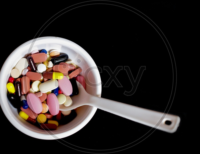 Bowl Of Medicine Pills Tablets Capsules In Black Background