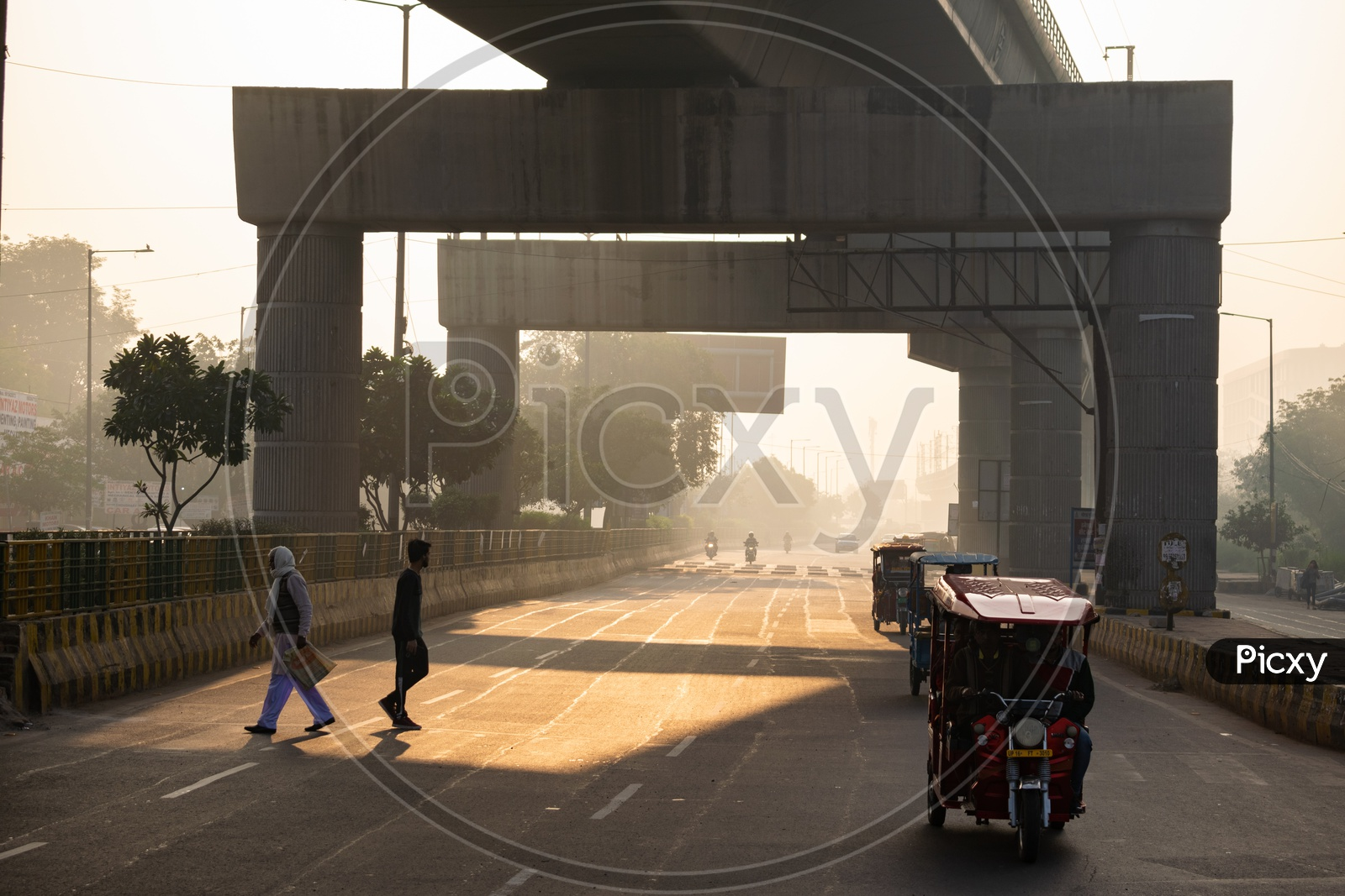 Metro line passing over a road and vehicles and people in a foggy morning