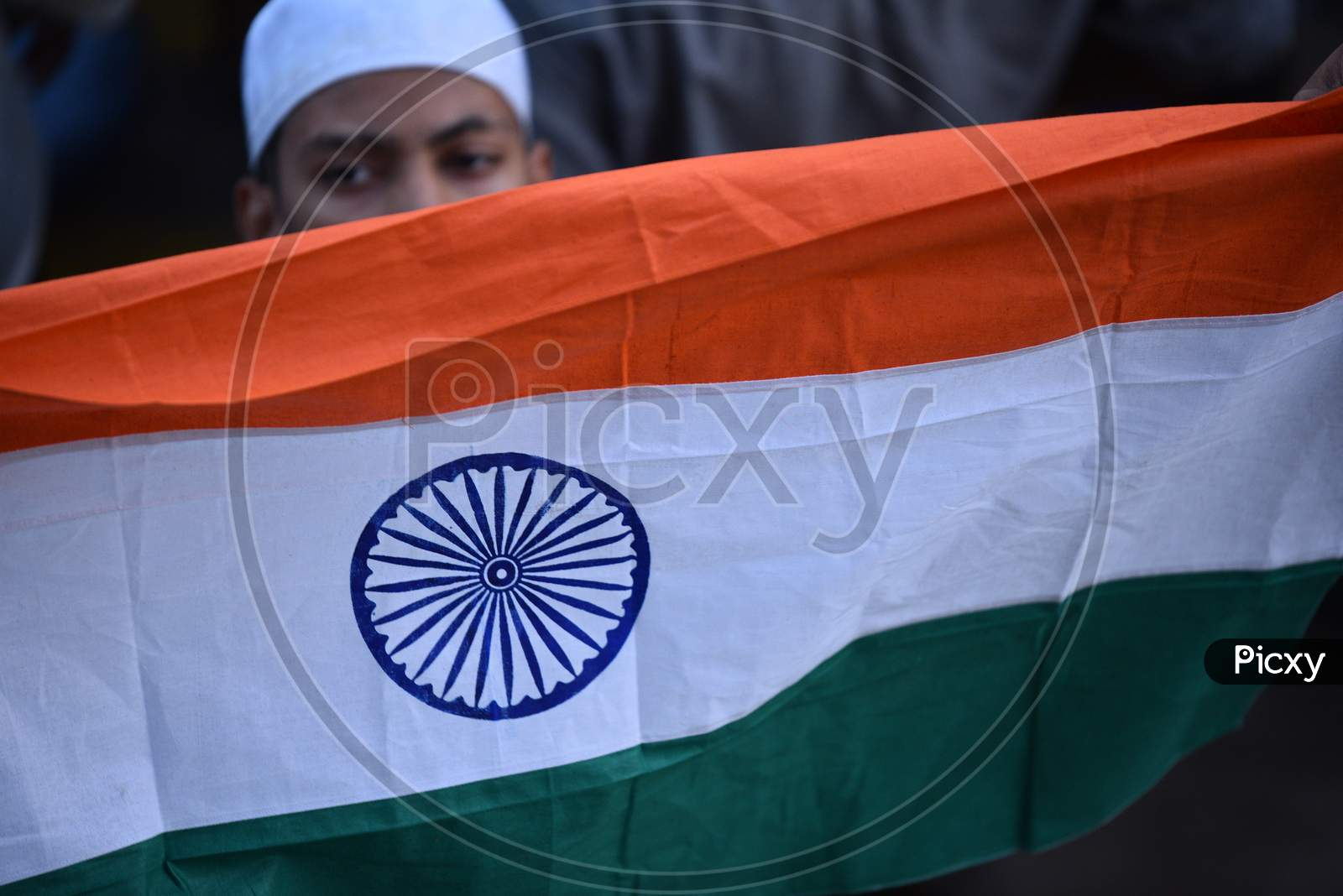 A muslim protester holds Indian Flag while demonstrating against CAA 2019 Act