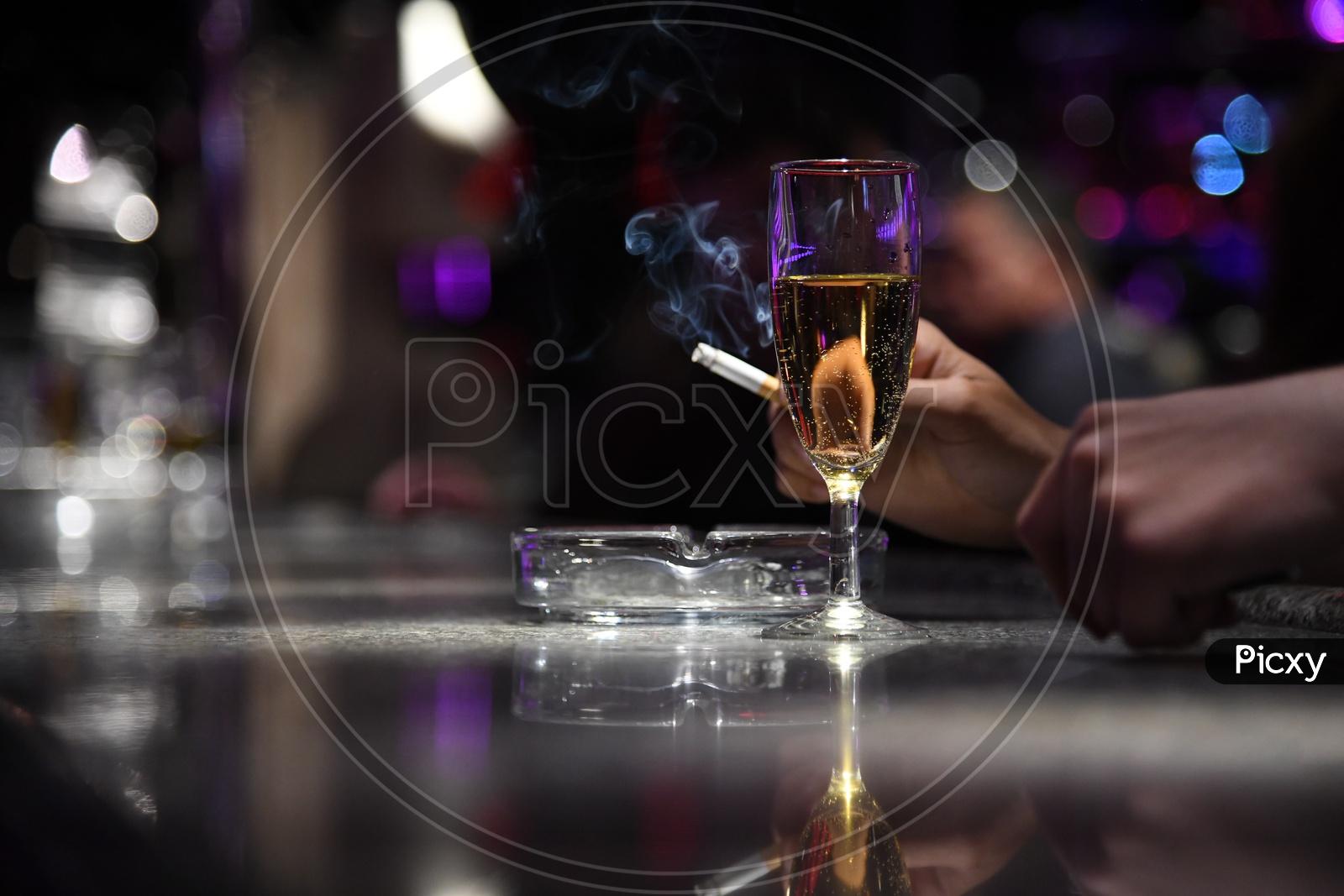 A Wine Glass With A Man Smoking Cigarette Hand Closeup