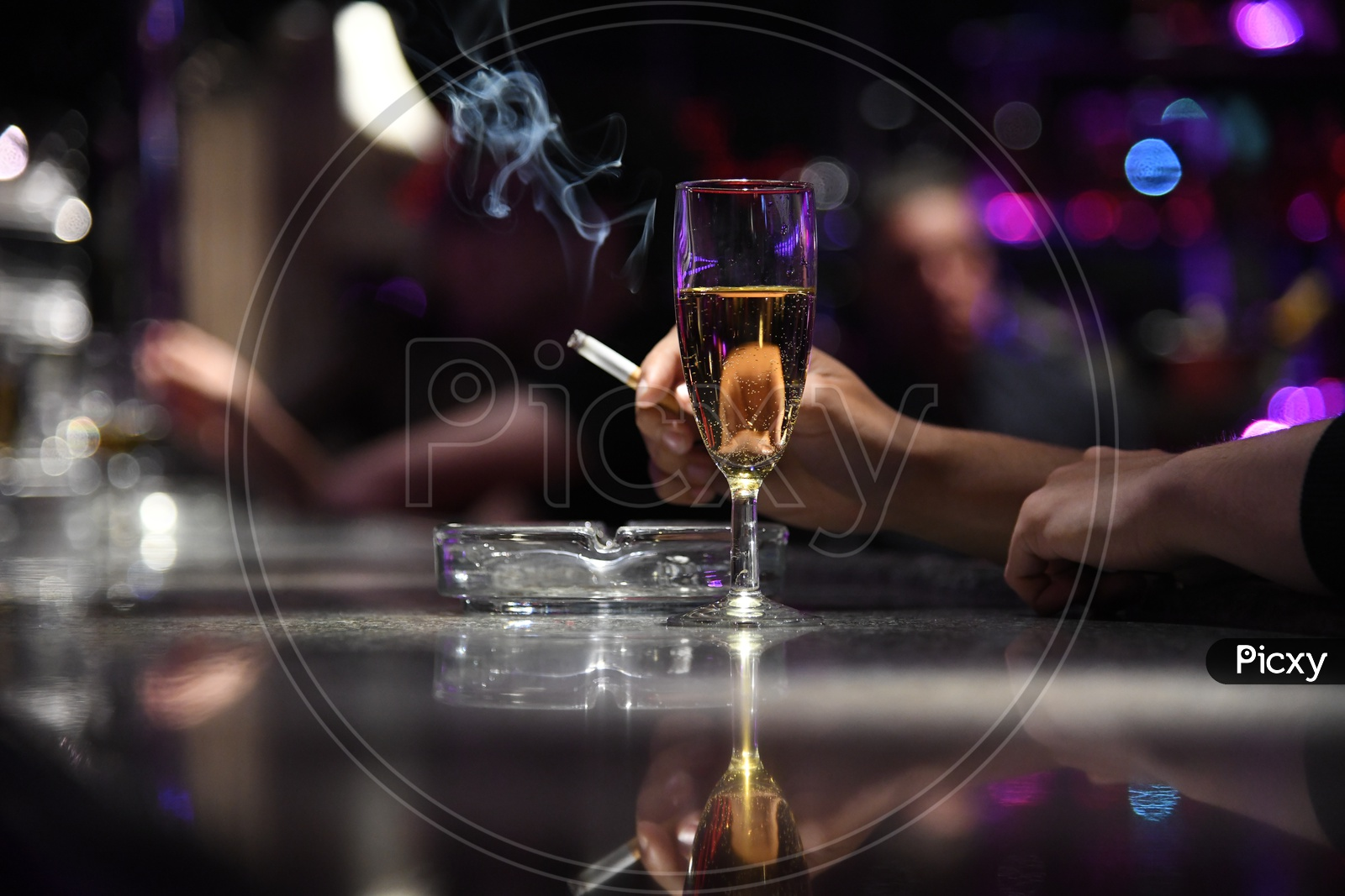 A Wine Glass With a Man Holding Cigarette in Hand Closeup