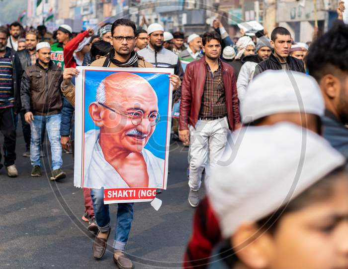 A man holding the picture of Mahatma Gandhi and others Protesting Against Caa And Nrc