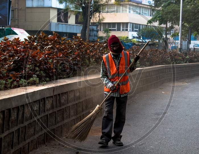 A GHMC Sweeper Cleaning Hyderabad City Roads In an Winter Morning