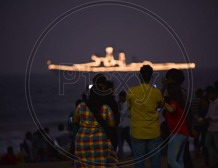 People watch an Indian Navy Ship in Visakhapatnam