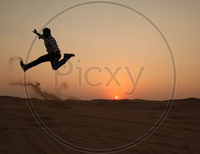 Silhouette of a man Jumping With Joy In Desert with a sunset In Background