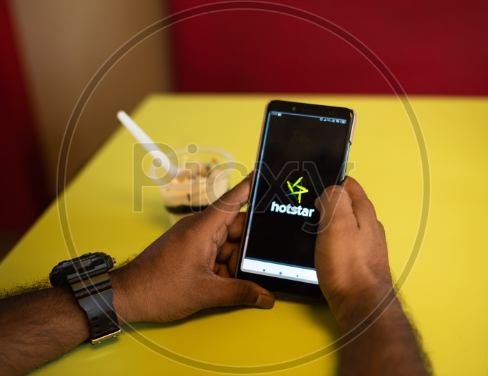 Indian youth using Hotstar Online streaming App in Mobile Phone