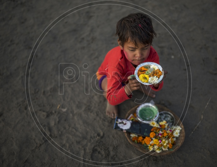 Local kid selling flowers in a plastic bowl