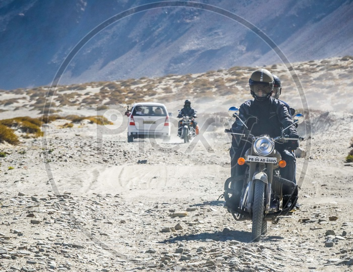 Riders riding motorcycle on the sand dunes alongside the Nubra Valley
