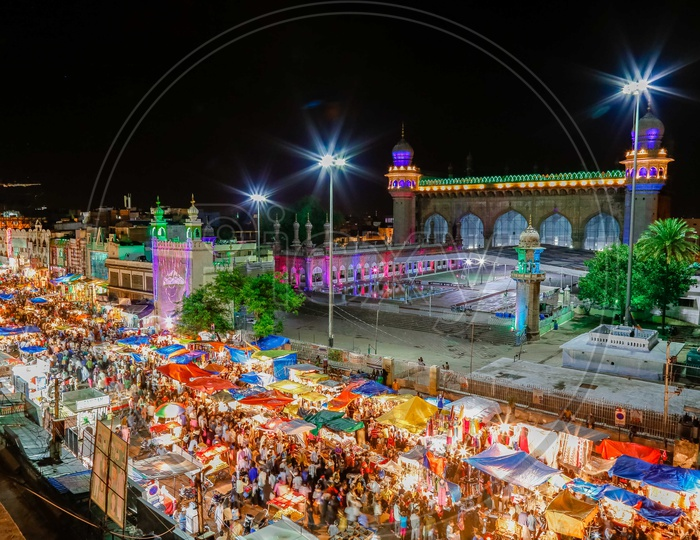 Crowd in the street alongside the Mecca Masjid during the night