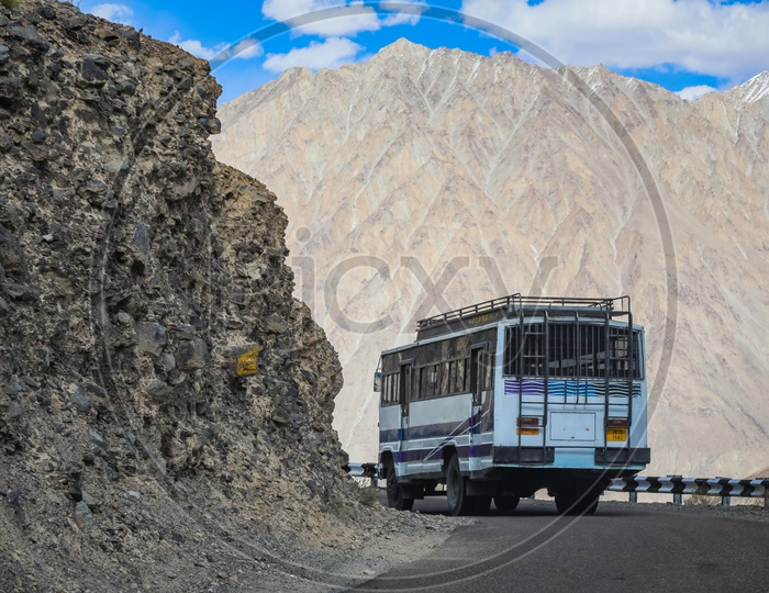 Moving bus on the roadway by the mountains
