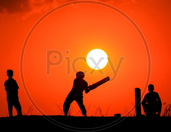 Street Kids Playing Cricket and Sunset in Background