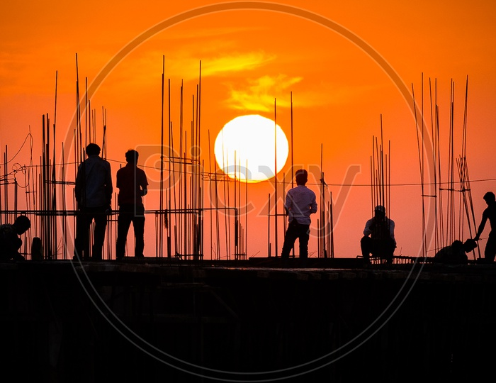 Construction Workers working and Sun in Background