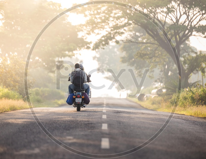 Two men riding Royal Enfield Motorcycle on the road