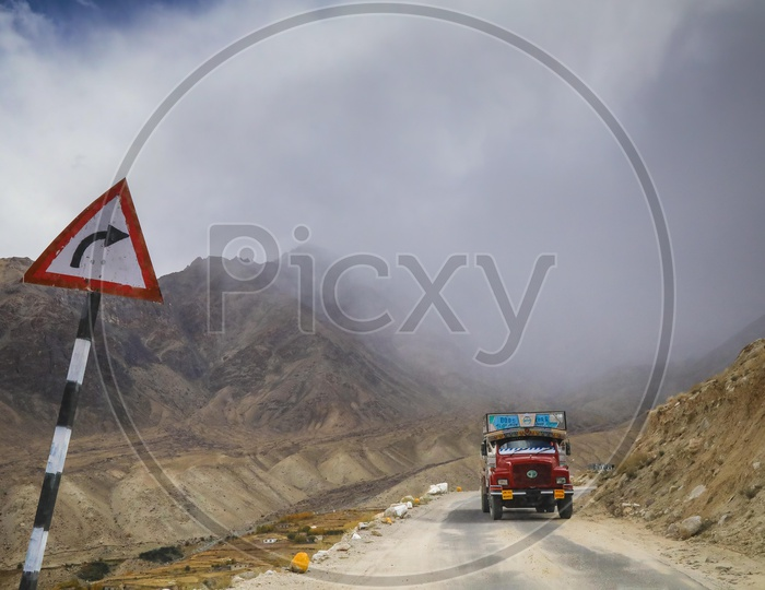 Lorry running on the rural road alongside the mountains with dark clouds covered in background